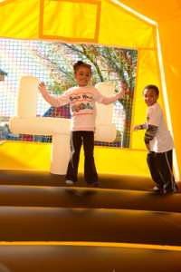 girl bouncing in yellow bounce house