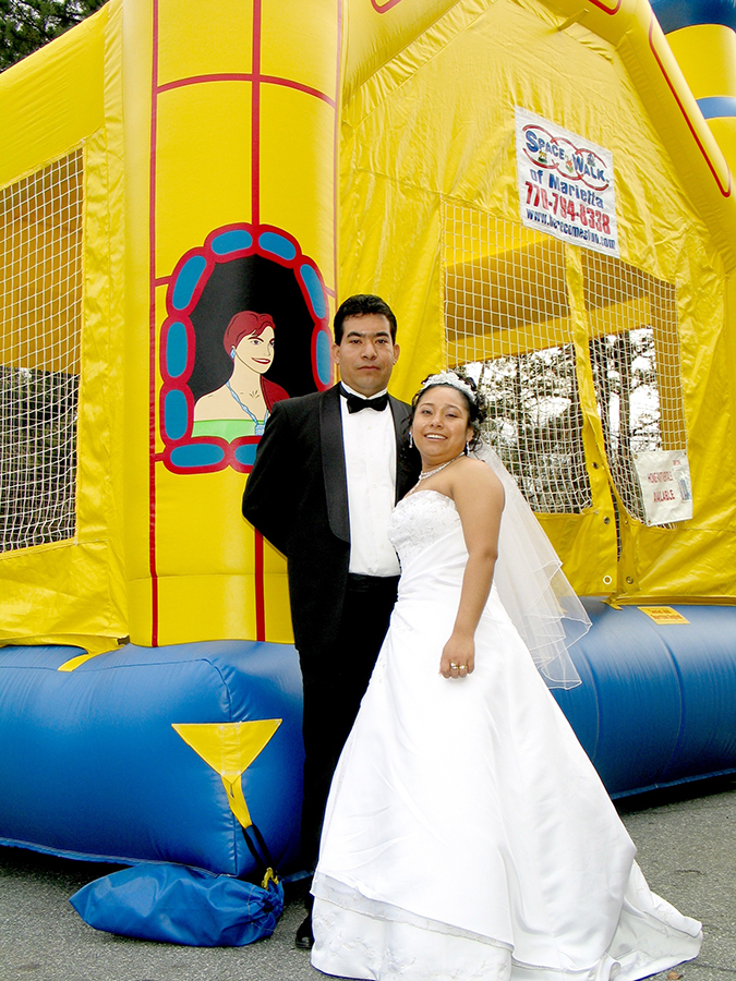 bride and groom with a bounce house